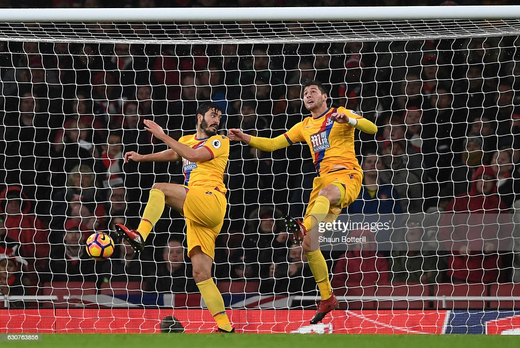 Neither James Tomkins or Joel Ward of Crystal Palace can prevent Alex Iwobi (not seen) of Arsenal from scoring his team's second goal during the Premier League match between Arsenal and Crystal Palace at the Emirates Stadium on January 1, 2017 in London, England.