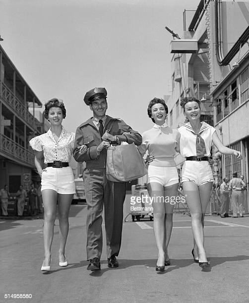 Neither rain nor sleet nor pretty girls keeps Hollywood postman from his appointed rounds at the Columbia Studios Joe who will attend the convention...