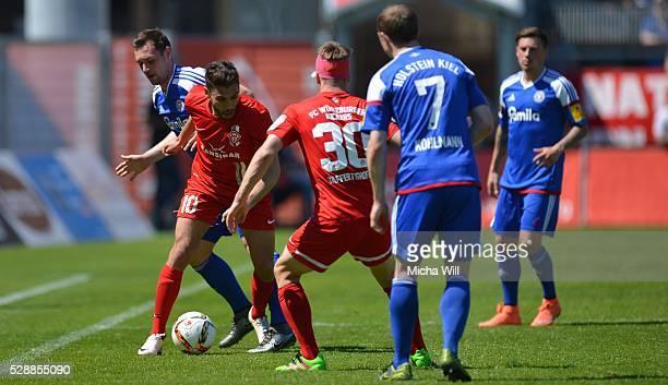 Nejmeddin Daghfous of Wuerzburg is challenged by Maik Kegel of Kiel during the Third League match between Wuerzburger Kickers and Holstein Kiel at...
