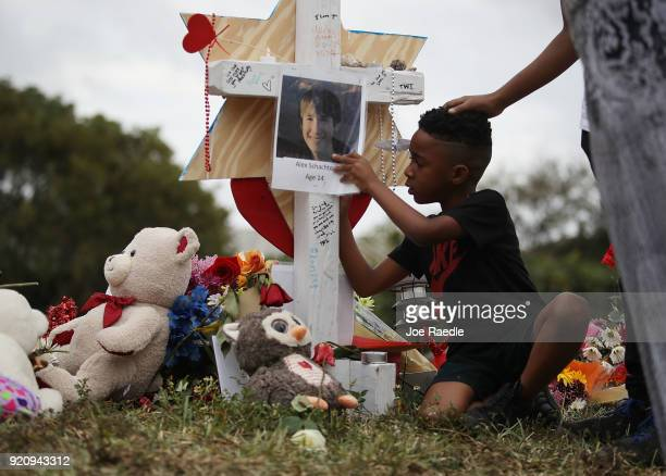 Nekhi Charlemagne writes a message on a cross setup in a makeshift memorial in front of Marjory Stoneman Douglas High School on February 19 2018 in...