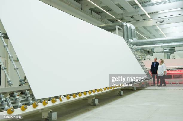 Nelli Diller manager of Seele GmbH and Tim Cook CEO of Apple Inc look at one of the sheets of glass for the new Apple Campus 2 during a factory visit...