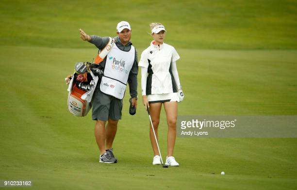 Nelly Korda and her caddie line up her second shot on the 7th hole during the first round of the Pure Silk Bahamas LPGA Classic at the Ocean Club...