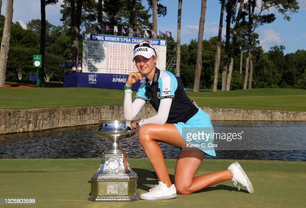 Nelly Korda poses with the trophy after putting in to win on the 18th green during the final round of the KPMG Women's PGA Championship at Atlanta...