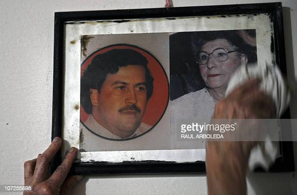 Nelly Rojas cleans the picture of Colombian drug lord Pablo Escobar inside her house at Pablo Escobar neighborhood on December 1 2010 in Medellin...