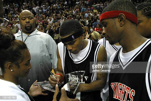 Nelly signs Chilli's trophy while Usher looks on