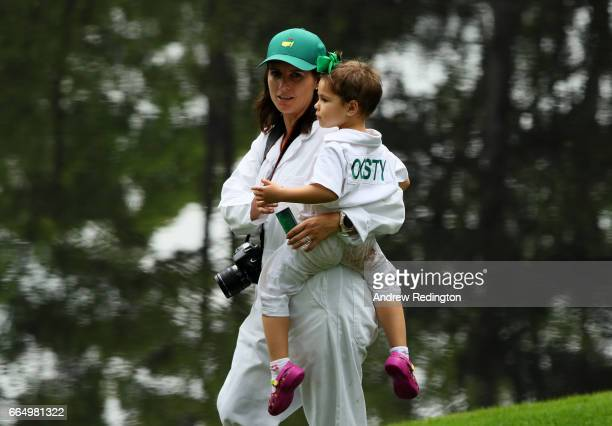 NelMare wife of Louis Oosthuizen of South Africa holds one of their three daughters during the Par 3 Contest prior to the start of the 2017 Masters...