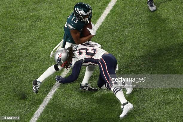 Nelson Agholor of the Philadelphia Eagles carries the ball defended by Stephon Gilmore of the New England Patriots in Super Bowl LII at US Bank...
