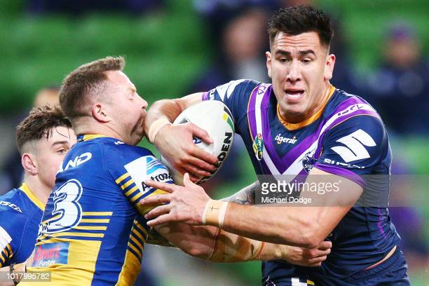 Nelson Asofa Solomona of the Storm runs with the ball through Nathan Brown of the Eels during the round 23 NRL match between the Melbourne Storm and...