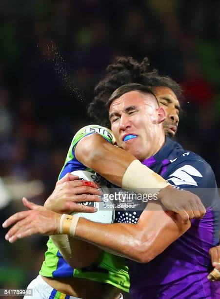 Nelson AsofaSolomona of the Storm is tackled by Iosia Soliola of the Raiders during the round 26 NRL match between the Melbourne Storm and the...