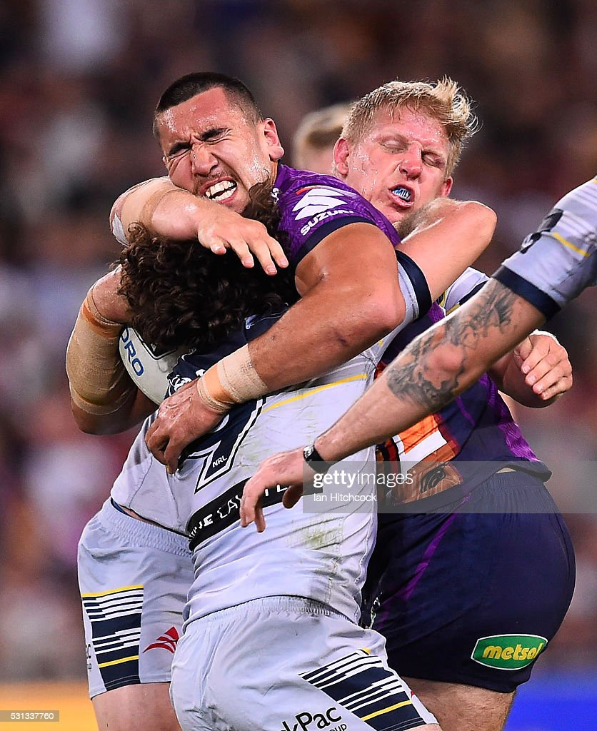Nelson Asofa-Solomona of the Storm is tackled by Jake Granville and Ben Hannant of the Cowboys during the round 10 NRL match between the Melbourne Storm and the North Queensland Cowboys at Suncorp Stadium on May 14, 2016 in Brisbane, Australia.