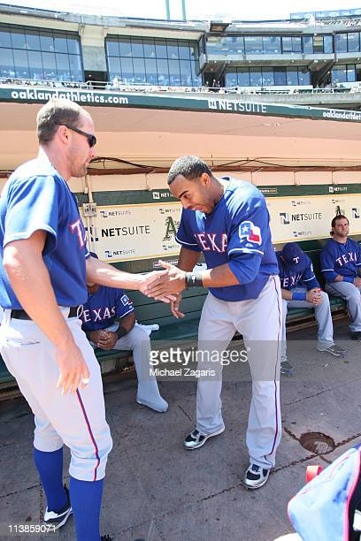 Nelson Cruz and David Murphy of the Texas Rangers engage in pregame ritual in the dugout before before the game against the Oakland Athletics at the...