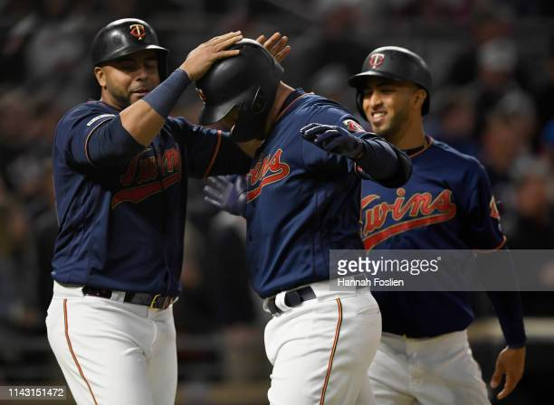 Nelson Cruz CJ Cron and Eddie Rosario of the Minnesota Twins celebrate a threerun home run by Cron against the Detroit Tigers during the fifth inning...
