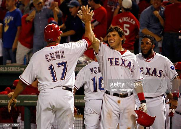 Nelson Cruz, Ian Kinsler and Elvis Andrus of the Texas Rangers celebrate after Cruz scored on a two-run double by Mike Napoli in the eighth inning...