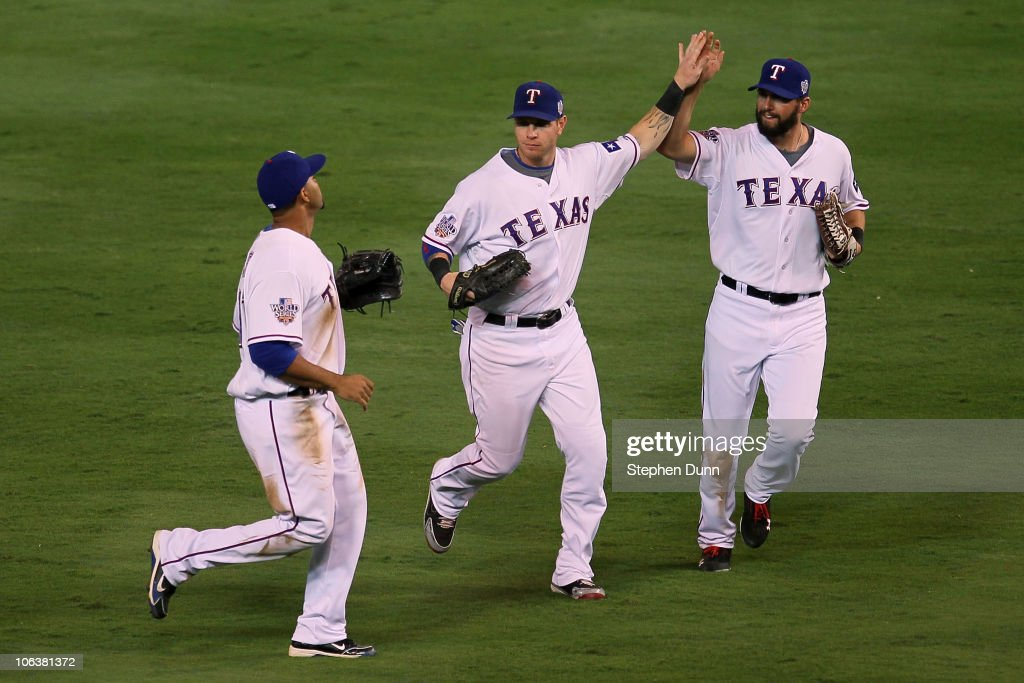 Nelson Cruz #17, Josh Hamilton #32 and Jeff Francoeur #21 of the Texas Rangers celebrate after their 4-2 win against the San Francisco Giants in Game Three of the 2010 MLB World Series at Rangers Ballpark in Arlington on October 30, 2010 in Arlington, Texas.