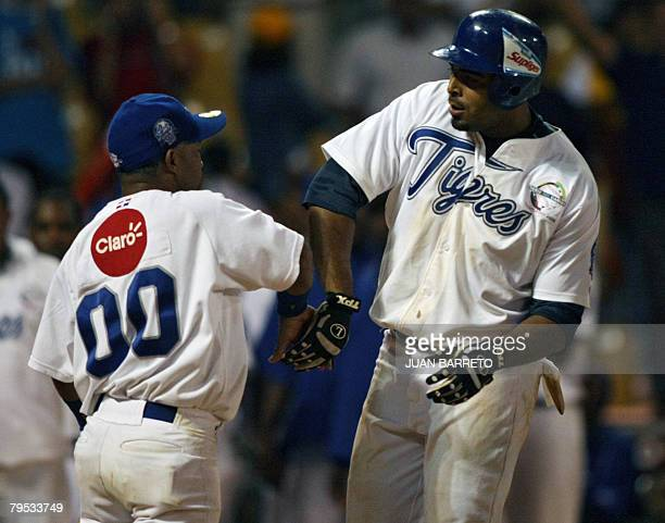 Nelson Cruz of Dominican Tigres de Licey celebrates with the bat boy after making a home run during a Caribbean Series' baseball game against...