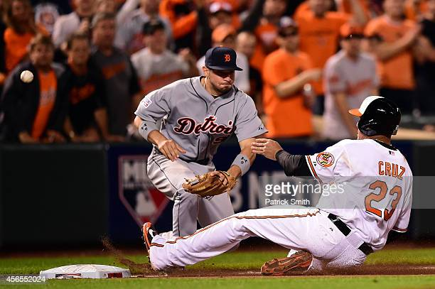 Nelson Cruz of the Baltimore Orioles slides safe to third base against Nick Castellanos of the Detroit Tigers in the eighth inning during Game One of...