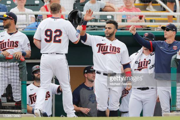 Nelson Cruz of the Minnesota Twins celebrates with Cody Asche after he scored a run against the Philadelphia Phillies in the fifth inning of a...