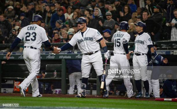 Nelson Cruz of the Seattle Mariners and Kyle Seager of the Seattle Mariners are congratulated by Daniel Vogelbach of the Seattle Mariners and Ichiro...