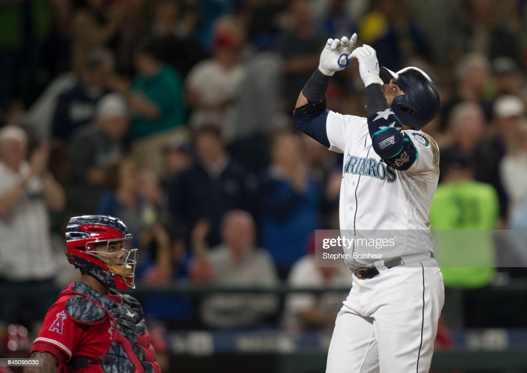 Nelson Cruz #23 of the Seattle Mariners celebrates hitting a three-run home run off of relief pitcher Blake Wood #46 of the Los Angeles Angels of Anaheim that also scored Robinson Cano #22 of the Seattle Mariners and Mitch Haniger #17 of the Seattle Mariners during the fourth inning of a game at Safeco Field on September 9, 2017 in Seattle, Washington. At left, is catcher Martin Maldonado #12 of the Los Angeles Angels of Anaheim.