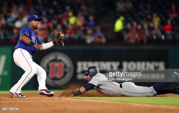 Nelson Cruz of the Seattle Mariners dives into second base safe against Elvis Andrus of the Texas Rangers on a wild pitch by Andrew Cashner of the...