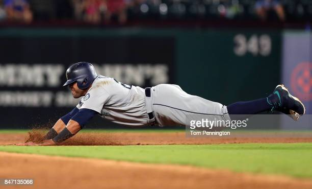 Nelson Cruz of the Seattle Mariners dives into second base safe on a wild pitch by Andrew Cashner of the Texas Rangers in the top of the third inning...