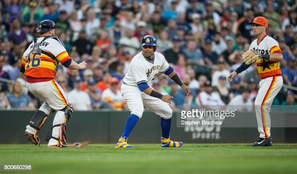 Nelson Cruz of the Seattle Mariners gets caught in a run down between catcher Brian McCann of the Houston Astros and third baseman Alex Bregman of...