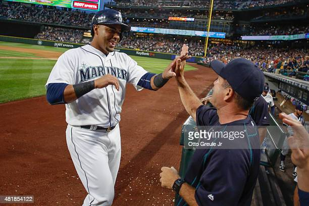 Nelson Cruz of the Seattle Mariners is congratulated by hitting coach Edgar Martinez after scoring on a tworun triple off the bat of Robinson Cano in...