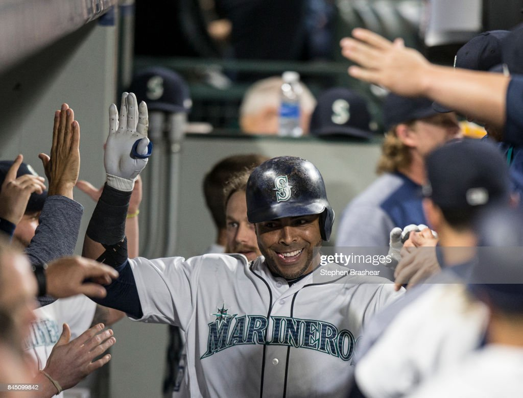 Nelson Cruz #23 of the Seattle Mariners is congratulated by teammates in the dugout after hitting a three-run home run off of relief pitcher Jesse Chavez #40 of the Los Angeles Angels of Anaheim that also scored Robinson Cano #22 of the Seattle Mariners and Mitch Haniger #17 of the Seattle Mariners during the sixth inning of a game at Safeco Field on September 9, 2017 in Seattle, Washington.
