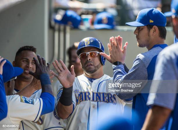 Nelson Cruz of the Seattle Mariners is congratulated by teammates including Hisashi Iwakuma right of the Seattle Mariners after scoring a run on a...