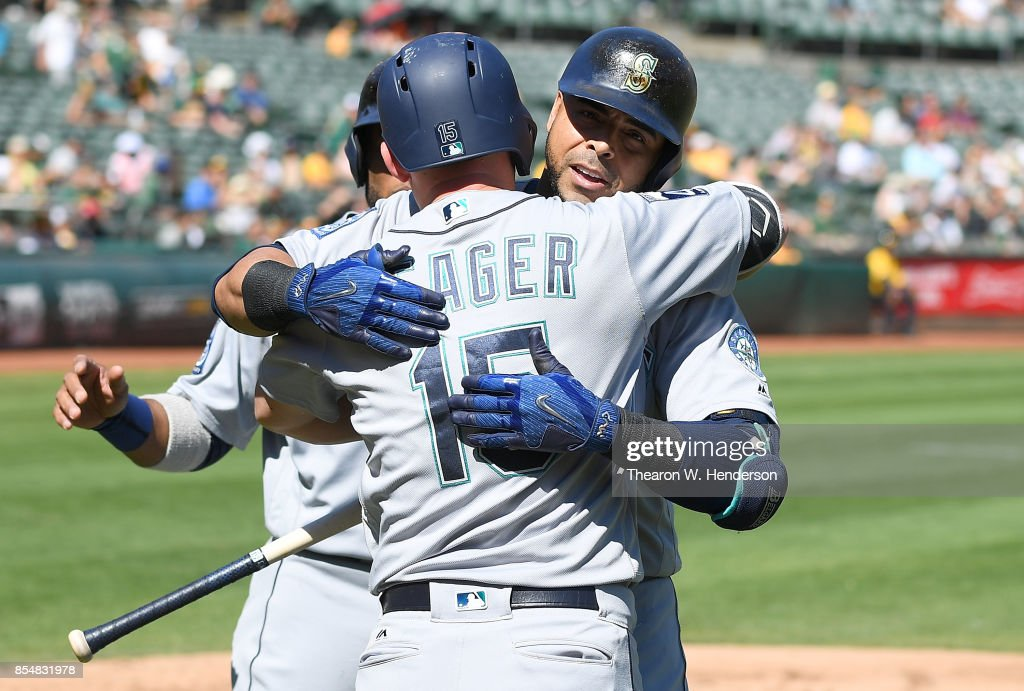 Nelson Cruz #23 of the Seattle Mariners is greated with a hug from Kyle Seager #15 after Cruz hit a two-run homer against the Oakland Athletics in the top of the fourth inning at Oakland Alameda Coliseum on September 27, 2017 in Oakland, California.