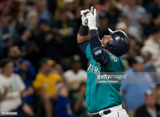 Nelson Cruz of the Seattle Mariners points skyward as he come home after hitting a three run home run his 300th off of Liam Hendriks of the Oakland...