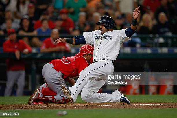Nelson Cruz of the Seattle Mariners scores against catcher Carlos Perez of the Los Angeles Angels of Anaheim on an RBI single off the bat of Mark...