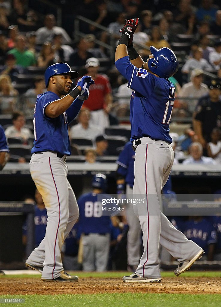 Nelson Cruz #17 of the Texas Rangers celebrates with Elvis Andrus #1 after hitting a two run home run against the New York Yankees in the at Yankee Stadium on June 26, 2013 in the Bronx borough of New York City.