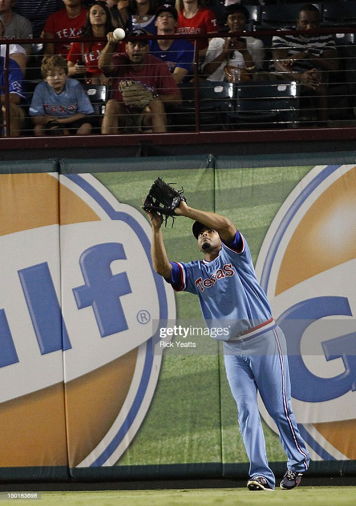 Nelson Cruz #17 of the Texas Rangers fields a fly ball hit by Omar Infante of the Detroit Tigers at Rangers Ballpark in Arlington on August 11, 2012 in Arlington, Texas.