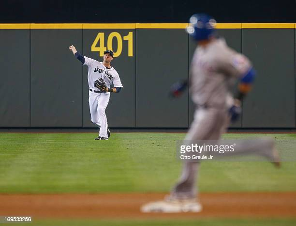 Nelson Cruz of the Texas Rangers rounds second base trying to stretch a double into a triple as center fielder Michael Saunders of the Seattle...