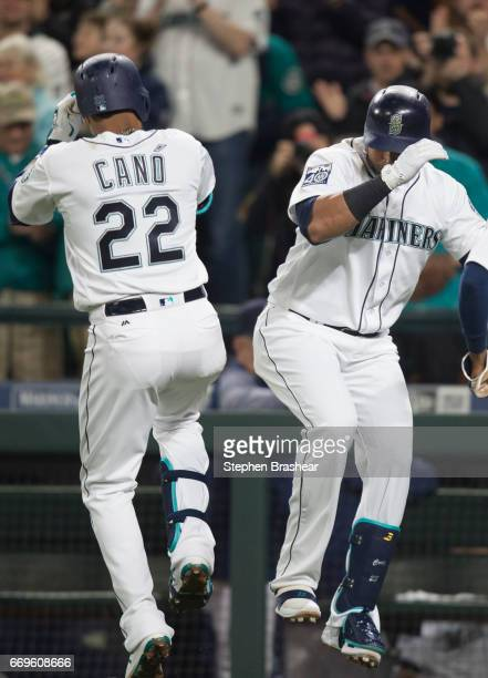 Nelson Cruz right of the Seattle Mariners and Robinson Cano of the Seattle Mariners celebrate a tworun home run by Cano off of starting pitcher Tom...