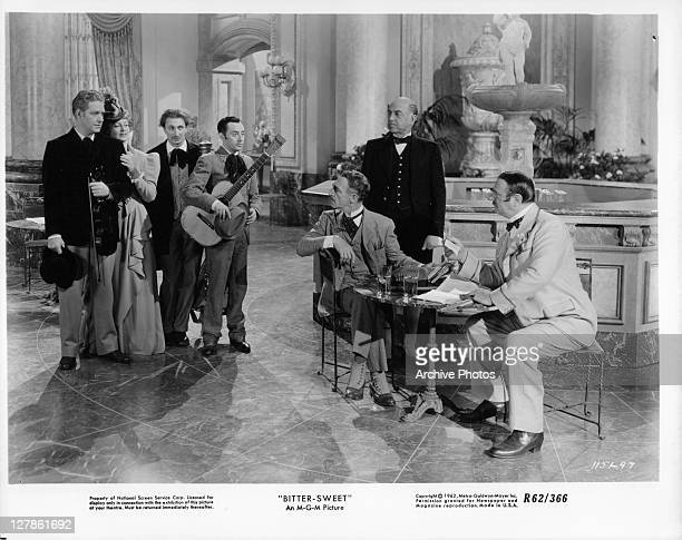 Nelson Eddy holding violin while Jeanette MacDonald holds onto him in front of unidentified men in a scene from the film 'Bitter Sweet' 1940