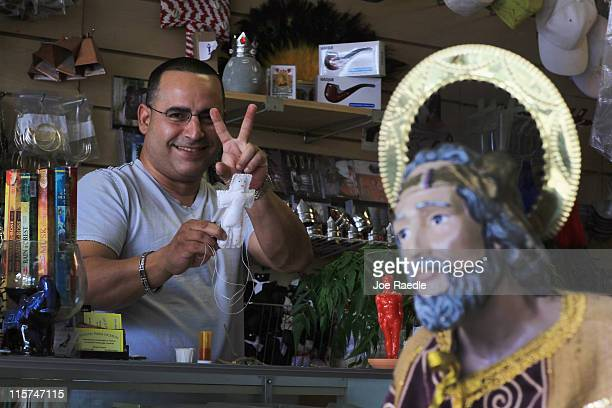 Nelson Hernandez flashes the victory sign as he shows off one of the voodoo dolls that he is selling at El Viejo Lazaro Botanica to try and help the...