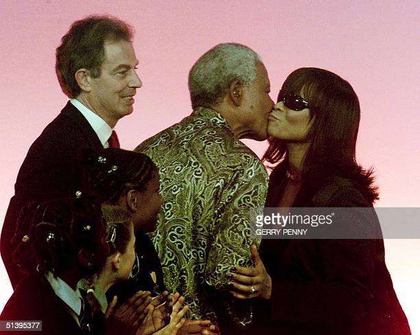 Nelson Mandela receives a kiss from singer Gabrielle watched by British Prime Minister Tony Blair and school children after the former South African...
