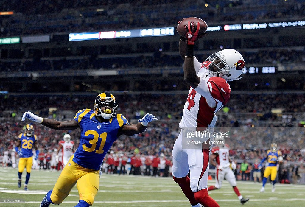 J.J. Nelson #14 of the Arizona Cardinals catches a pass for a touchdown while under pressure from Maurice Alexander #31 of the St. Louis Rams in the first quarter at the Edward Jones Dome on December 6, 2015 in St. Louis, Missouri.