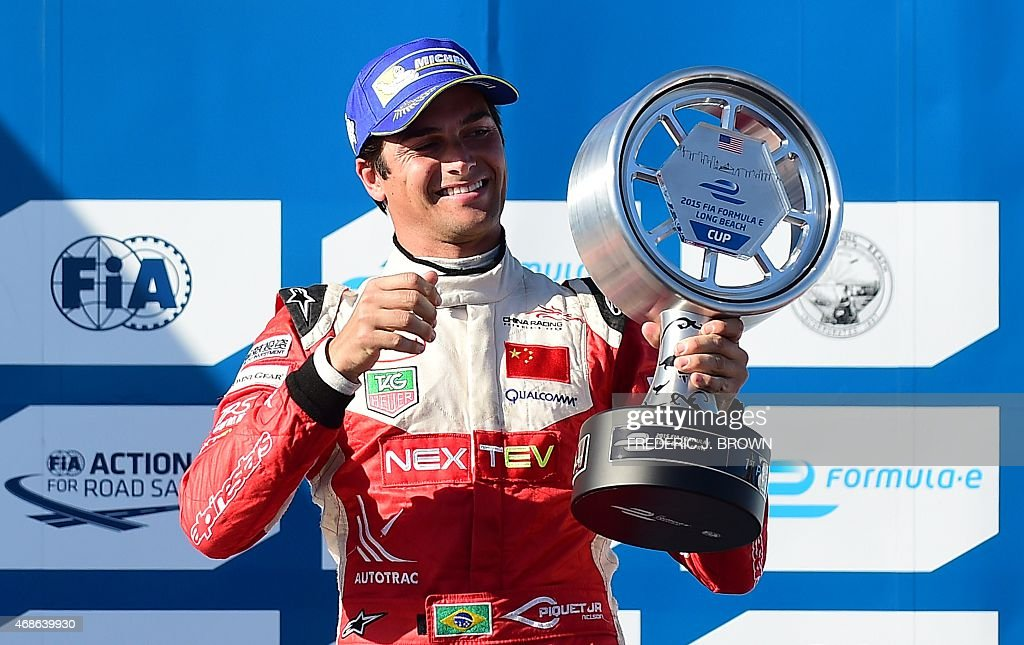 Nelson Piquet Jr. celebrates on the podium with the trophy after winning the inaugural Formula E Long Beach ePrix race in Long Beach, California on April 4, 2015 as the city hosted round 6 of the 11-round 2014-2015 FIE Formula E Series. Piquet Jr. finished ahead of Jean-Eric Vergne, 2nd, and Lucas di Grassi, 3rd.