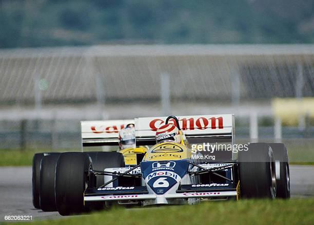 Nelson Piquet of Brazil drives the Canon Williams Honda Williams FW11 Honda V6T turbo ahead of team mate Nigel Mansell during the Brazilian Grand...