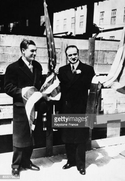 Nelson Rockefeller et un attaché de l'ambassade française échangeant les drapeaux à l'occasion de l'inauguration de la maison française du Rockfeller...
