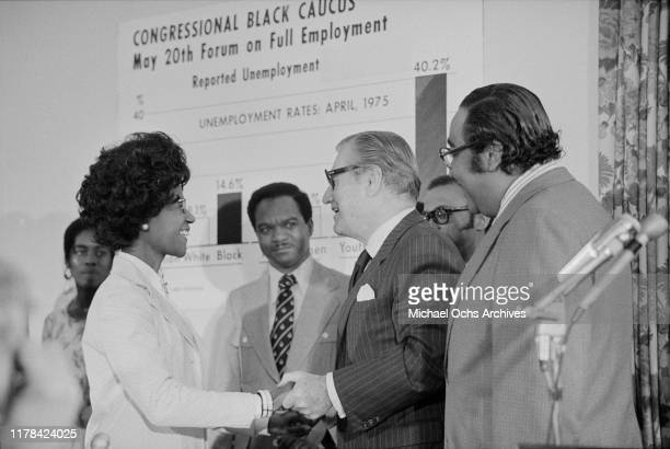 Nelson Rockefeller shaking hands with Rep Shirley Chisholm as Rep Walter Fauntroy Rep Charles Rangel and others look on at the congressional Black...