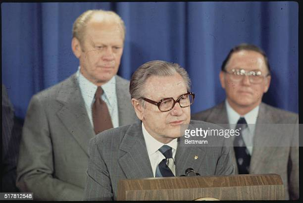Nelson Rockefeller speaks as Gerald Ford and unknown look on