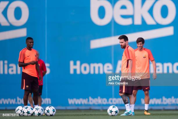Nelson Semedo and Lionel Messi of FC Barcelona look on during a training session ahead of the UEFA Champions League Group D match against Juventus on...