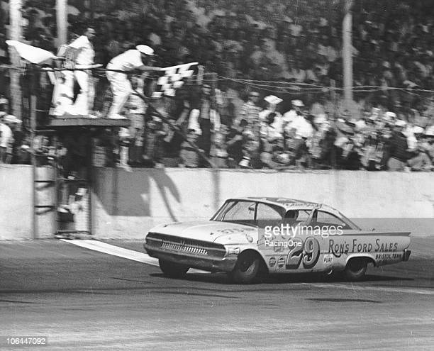 Nelson Stacy raises his arm in the air as he takes the checkered flag to win the Southern 500 at Darlington Raceway.