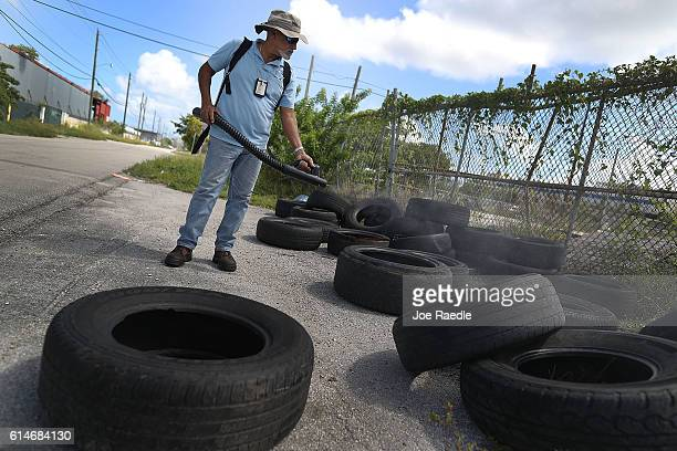 Nelson Tejeda a MiamiDade County mosquito control inspector uses a sprayer filled with a pesticide in an attempt to kill mosquitos that are carrying...