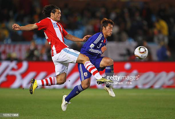 Nelson Valdez of Paraguay in action against Yuichi Komano of Japan during the 2010 FIFA World Cup South Africa Round of Sixteen match between...