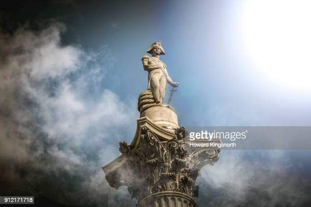 nelson's column in the clouds - nelson's column stock photos and pictures